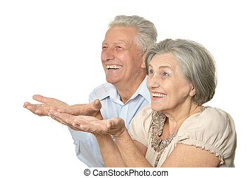 Older couple showing your product on a light background