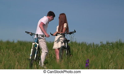 Young couple with bicycles in the green field - Young couple...