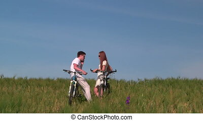 Teenage couple with bicycles in the green field, the guy...