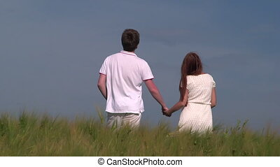Young couple holding hands in wheat field looking at the...