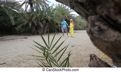 man and woman walk on the beach with palm trees