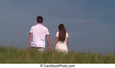 Young couple holding hands and walking through wheat field