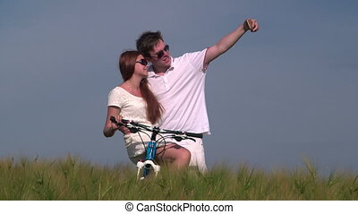 Young couple taking photo with smart phone in wheat field -...