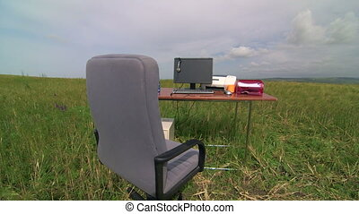 Remote virtual office - computer and supplies on a desk in...