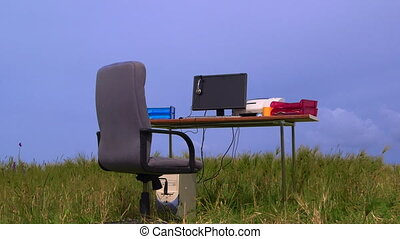 Personal computer on a desk in green field against blue sky