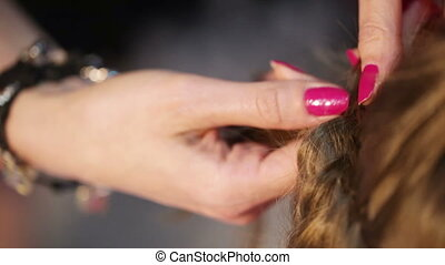 Gathering and braiding hair - Hairdresser collects and...