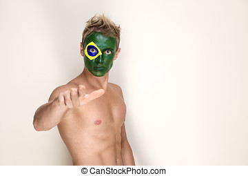 Soccer fan with brazil flag painted over face point by...