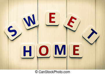 Sweet home word, composed of letters on a background of wood