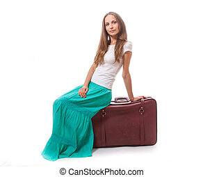 young woman sitting on a suitcase, isolated on white...
