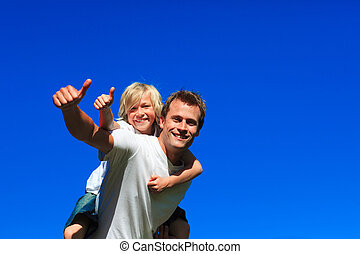 Son on father\'s back with thumbs up in a park