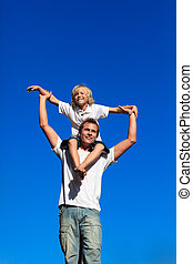 Boy sitting on his fathers shoulders - Little boy sitting on...