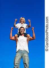Strong son sitting on his fathers shoulders against blue sky...