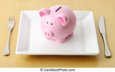 eating money - Piggy bank on the plate with fork and knife