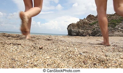 man and woman going into the sea - man and a woman going...