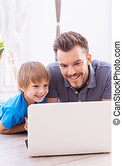 Surfing the net together. Happy father and son looking at...