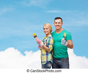 smiling couple with paintbrush - repair, construction and...