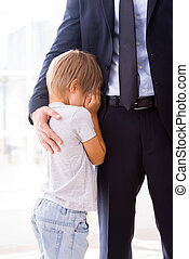I will be missing you! Little boy crying and covering face with hands while his father in formalwear consoling him