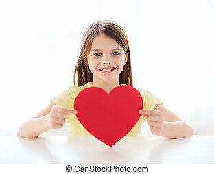 smiling little girl with red heart at home - love, home,...