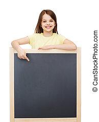 happy little girl pointing finger to blackboard - people,...