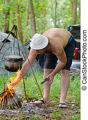 Man lighting a cooking fire while camping with a firelighter...