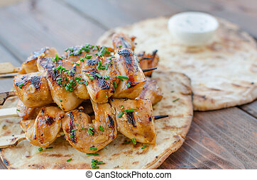 Grilled chicken skewers on grill with naan