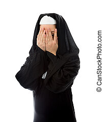 Young nun peeking through hands covering face - young...