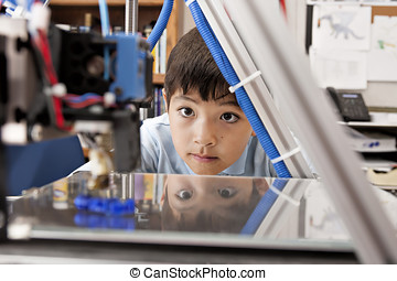 Boy watches machine intently. - A young boy watches as a 3D...