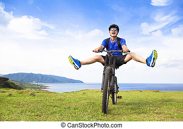 funny young backpacker riding a bicycle on a meadow