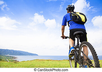 young man sitting on a  mountain bike and looking the ocean