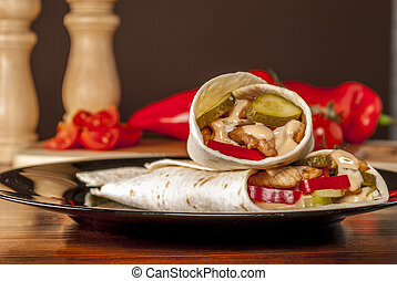 Tortilla with tomato and chicken meat and cucumber on black...