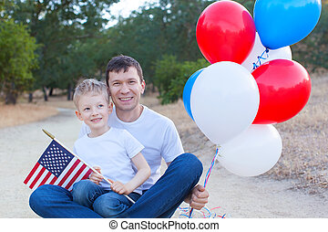 family celebrating 4th of July - handsome father holding...