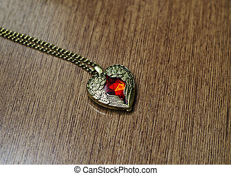 Pendant vitage heart shape on wooden background