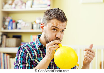 Father blowing balloon - happy father is blowing yellow...