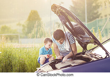 Father and son repairing car - Young father with his little...