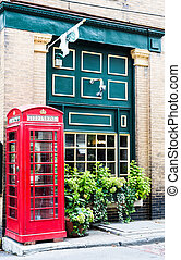 Red Phone Booth by Green Wall - A traditional red phone...