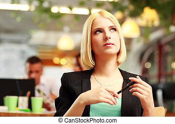 Portrait of a thoughtful blonde businesswoman looking up in...