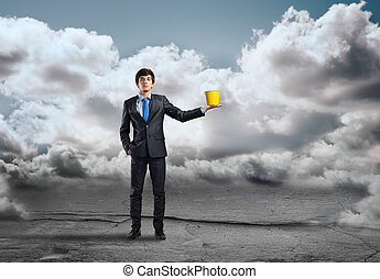 Man holding bucket - Young businessman holding yellow bucket...