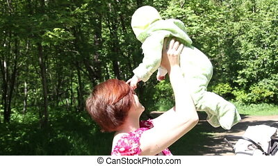 Mother playing her baby in park