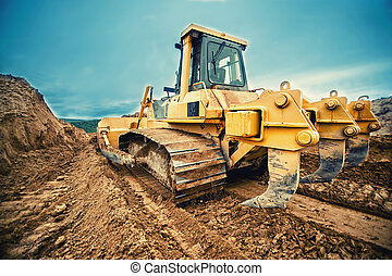 close-up of bulldozer or excavator working with soil on...