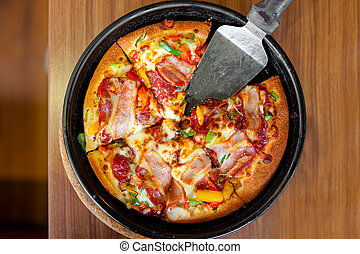 Supreme delicious fresh pizza with bacon, ham and vegetables...