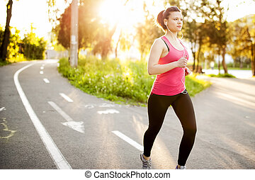 Atheletic fitness woman jogging outdoors in city park at...