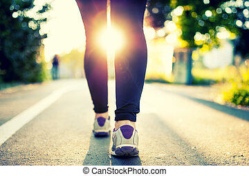Close-up of woman athlete feet and shoes while running in...