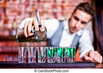 Bartender pouring blue curacao alcoholic cocktail in glasses...