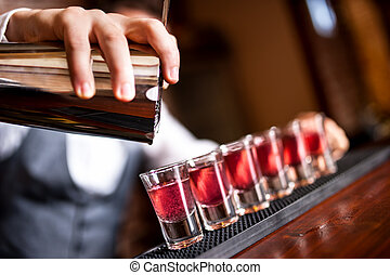 close-up of barman hand pouring alcohol into shot glasses in...