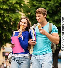 Beautiful students couple eating ice-cream outdoors