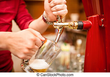 bartender pouring beer draft in pub, bar or nightclub