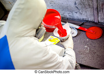Auto mechanic mixing and pouring red paint for spraying and...