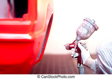 worker painting a red car or element in a special garage,...