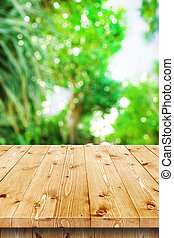 Empty wooden table in a sun drenched summer garden for...