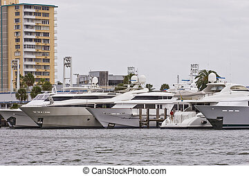 Row of White Yachts by Brown Condos